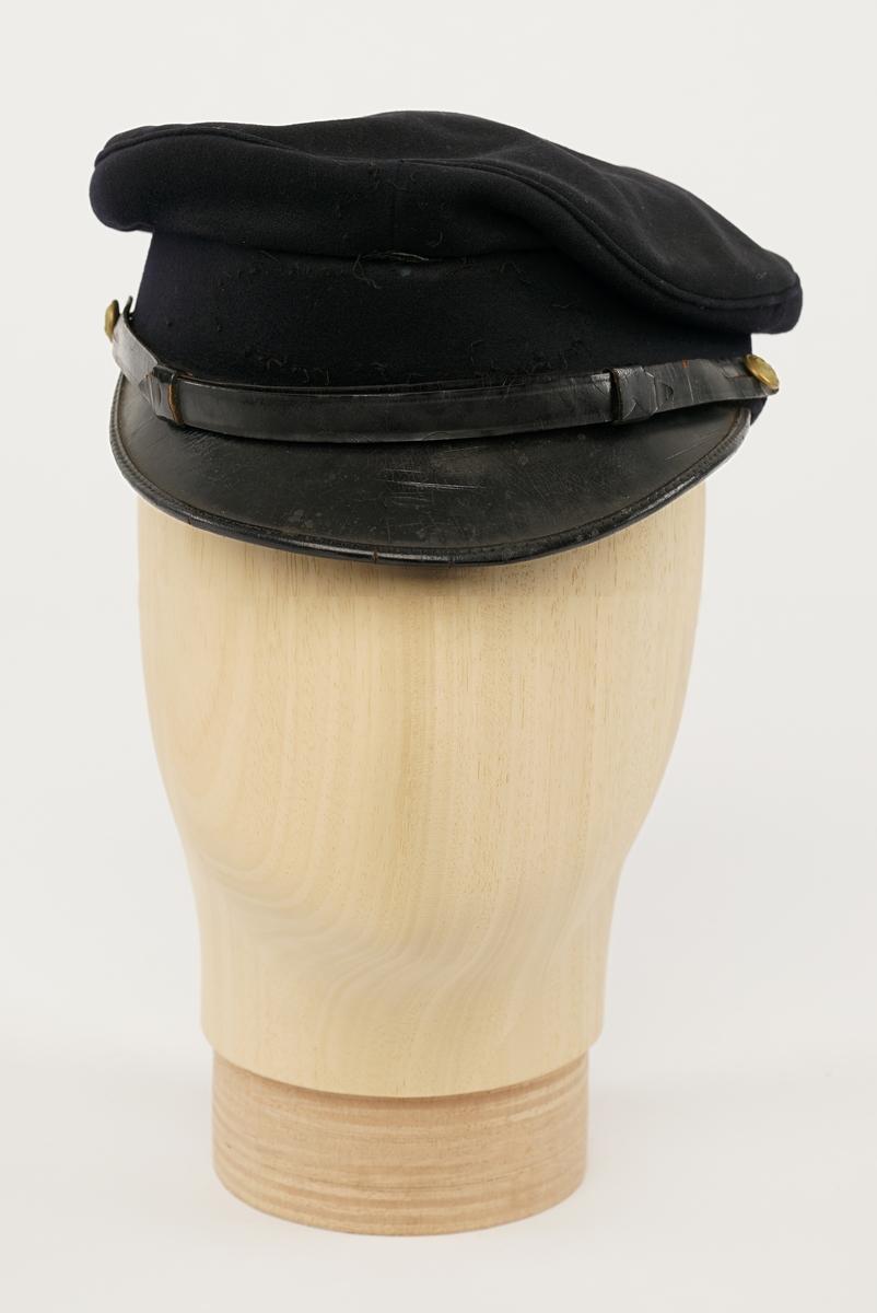 Mørkblå dame jakke enkelspent med fire riksløveknapper. Epauletter med merkurstav, krone, og to kvist eikblader (fire blader totalt) mellom to gullbånd. Tekstil marke på begge armer, krone over riksløve med hvit øks i rød skjold omgitt av eikeblader over TOLL/CUSTOMS. Hempe i nakke. Kypert stoff, blanding av polyester og ull. Jakke er foda med antatt syntetisk stoff, sort. Hvit hatt med sort visir. Metall distinkjons skilt av krone over riksløve med søkvferget øks i rød skjold omgitt av eikeblader. Gullfletting over visir, og eikeblader på visir. Lys blå dame skjorte med matchende distinktsjoner og tekstil merker på armene.
