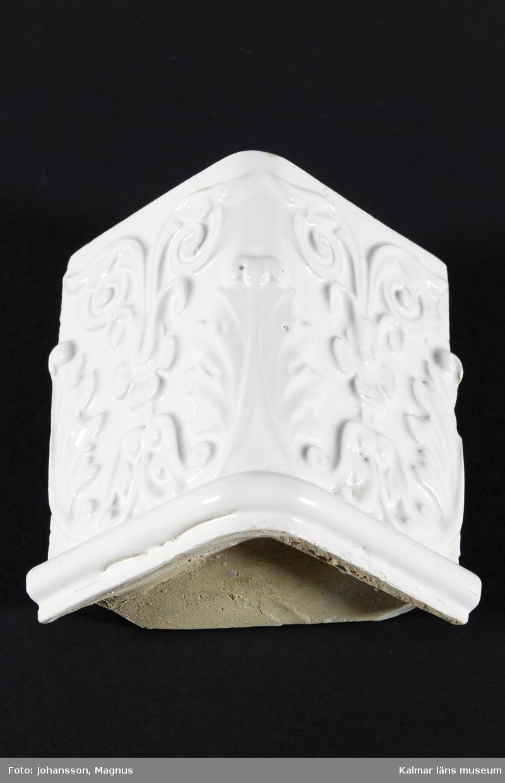 """KLM 38942. Kakel. Till flera ugnar. Tennvit glasyr på gulvit skärv. Handformpressade reliefkakel. Stildrag från Karl Johanstiden.  Förteckning över samtliga kakel, med mått inom parentes, gjord i samband med inventering 1997:   :1. 1 st. krönkakel         (10,5x24x7 cm)      5 st. fotsims            (11x28x9 cm)      4 st. friskakel           (13,5x25x6 cm) :2. 3 st. fotsims             (8,5x26x9 cm) återfanns ej vid inventering 2013. :3. 5 st. fotsims             (7,5x28,5x8 cm) övermålade med beige oljefärg. :4. 4 st. friskakel            (18x24x5,5 cm)       2 st. hörnfris            (18x17x10,5 cm) :5. 5 st. friskakel            (18x25x6,5 cm) har drejad rump. :6. 3 st. mittsims           (7,5x23x4 cm)     2 st.  -""""-                   (7,5x21x4 cm)     1 st. hörnmittsims    (6,5x16x12 cm) :7. 4 st. fotsims             (8x23x6,5 cm) med drejad rump.     1 st.  -""""-                   (8x17x6 cm)  -""""-       1 st. hörnfotsims      (6,5x18x14 cm)  -""""-       1 st.  -""""-                   (6,5x16x9,5 cm)  -""""-       3 st. mittsims           (6x21,5x5 cm)  -""""-       1 st. hörnmittsims    (5x16x11 cm)  -""""-       3 st. krönkakel         (15,5x26x5 cm)  -""""-       2 st.  -""""-                   (15,5x22x5 cm)  -""""-   :8. 4 st. fotsims             (11x24x9,5 cm)     1 st.  -""""-                   (11x21x9,5 cm)     2 st. hörnfotsims      (11x26x16,5 cm) :9. 5 st. krönkakel         (21,5x26x7,5 cm)     5 st. friskakel            (19,5x25x8,5 cm)"""