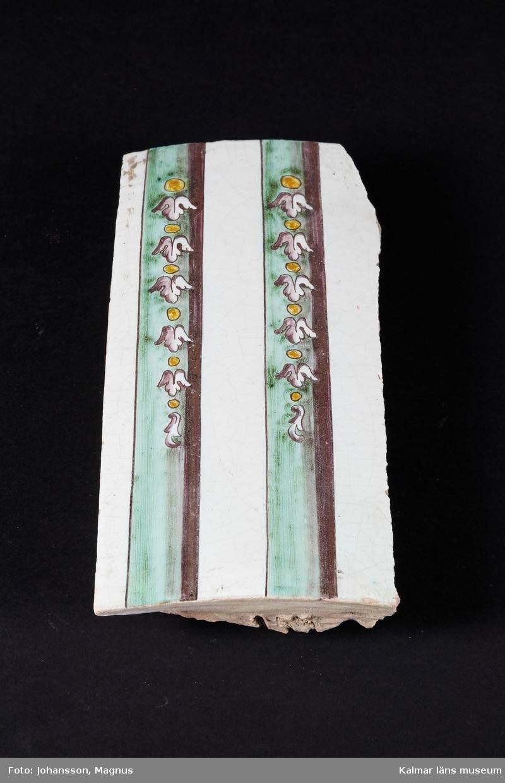 KLM 38946. Kakel. Kakelplattor till flera kakelugnar. Vit tennglasyr på gulröd lergodsskärv. Dekormålning i koppargrönt, manganlila, koboltblå och antimongult. Drejad rump.  Förteckning över samtliga kakel, med mått inom parentes, gjord i samband med inventering 1997:   :1. 3 st. fasadkakel, plana       (31,5x23,5x6 cm) :2. 3 st. hörnfasad, plana       (31,5x25,5x8 cm) :3. 2 st. fasadkakel, välvda     (32x19x7 cm)     4 st. fasadkakel, 1/2 lod    (32x11x3,5 cm)     2 st. fasadkakel, 1/2 lod    (32x11x4,5 cm) :4. 3 st. fotsims, plana           (15x24x3,5 cm)     1 st. hörnfotsims, plant     (15x28x9 cm)     3 st. fotsims, plana            (12x20,5x4,5 cm)     1 st. hörnfotsims, plant     (12x20,5x4,5 cm) :5. 1 st. mittsims, välvd         (10x21,5x10,5 cm) :6.1 st. simskakel, välvd         (10x10,5x4 cm) :7.1 st. krönsims, välvd          (13x19x2 cm) :8. 10 st. blandade fragment