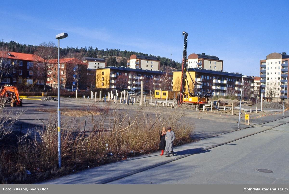 Pålning på Torallaplan i Bosgården, Mölndal, i april 1991. Vy från Torallastigen. Torallaplan skall bebyggas till hälften och resten göras iordning. Den stora asfaltsplanen var i dåligt skick. I bakgrunden ses bostadsbebyggelse vid Piltegatan och Häradsgatan. D 12:20.