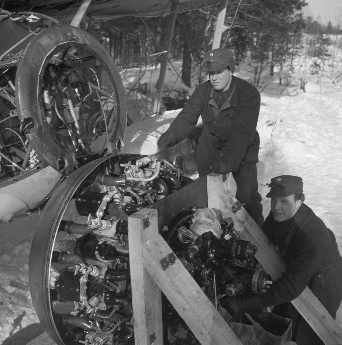 Demontering av motor på flygplan Gloster Gladiator efter Finska vinterkrigets slut i mitten av mars 1940 vid Svenska frivilligkåren i Finland, F 19. Två militärer i arbete.