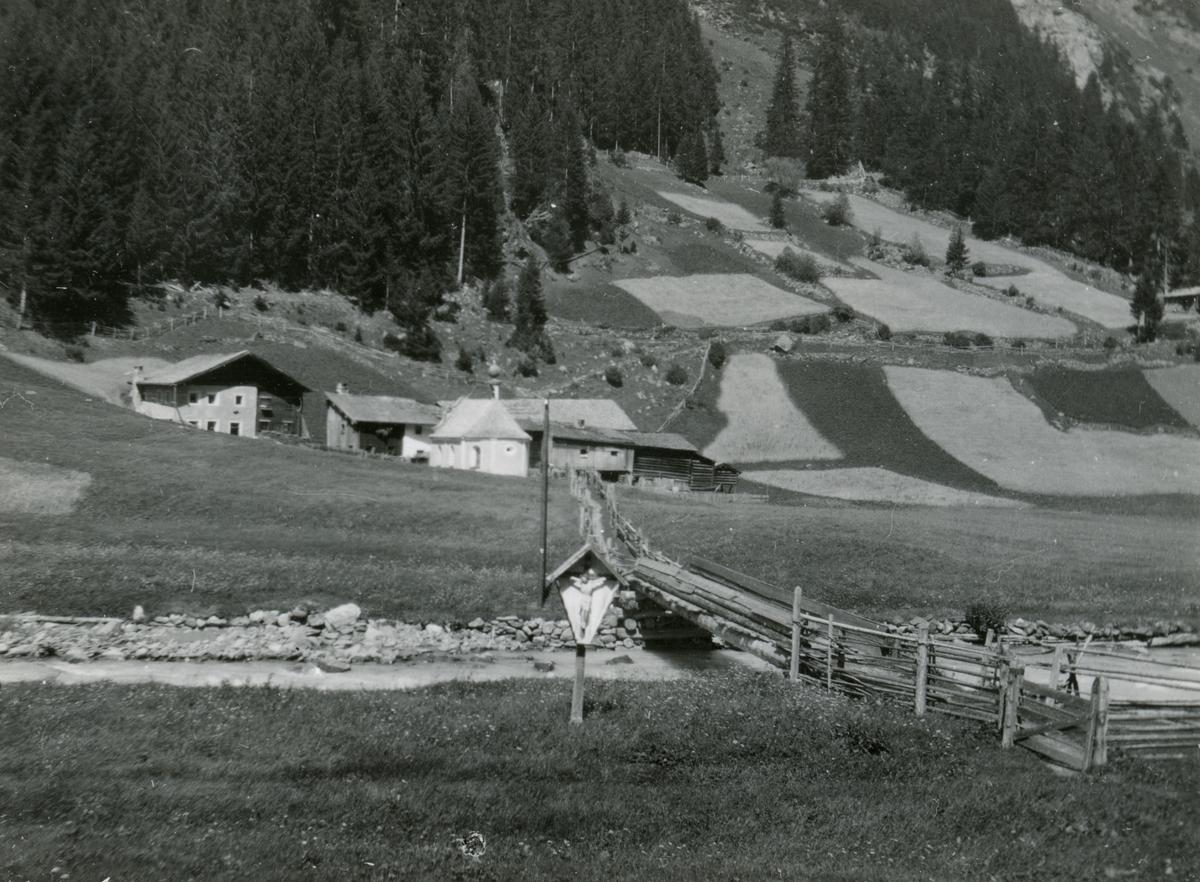 Prospektfotografi av en bondegård i Tirol, Italia. Ved veien står et Jesuskors.