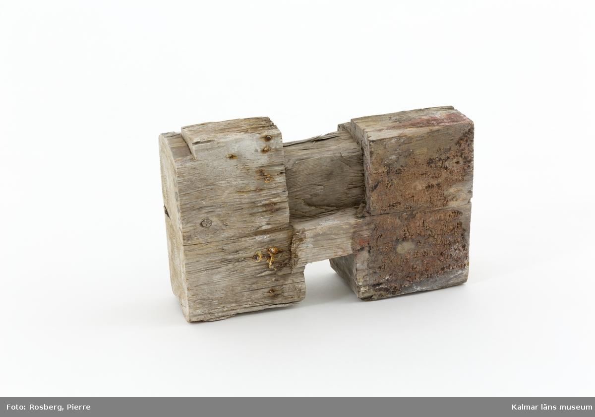 KLM 17282:2. Knuthuvud. Av trä. Delvis rödmålad och har runt om rester av murbruk. Knuthuvudet är försett med spikrader där tapet har suttit.