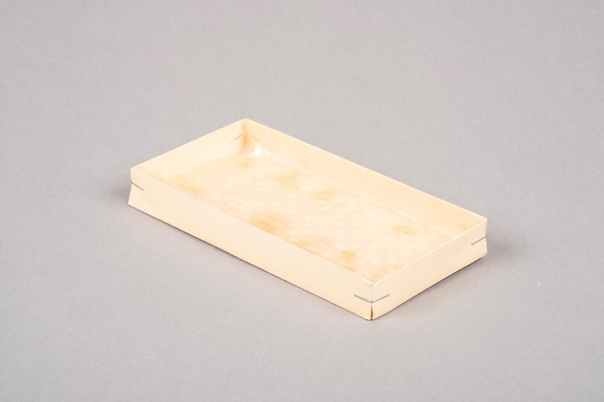 Bunn til konfekteske fra A. Bergene. Konfekten het Cabinet. Bunnen er i papp. Kantene er stiftet sammen. Inne i bunnen av esken ligger det beskyttelsespapir av to slag.