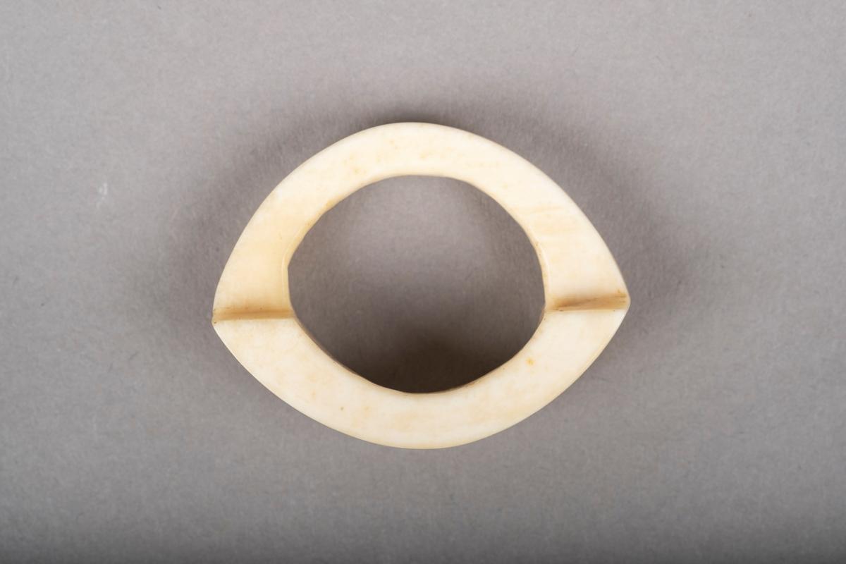 Ovalformet serviettring i ben. Påført tekst på fronten av serviettringen.