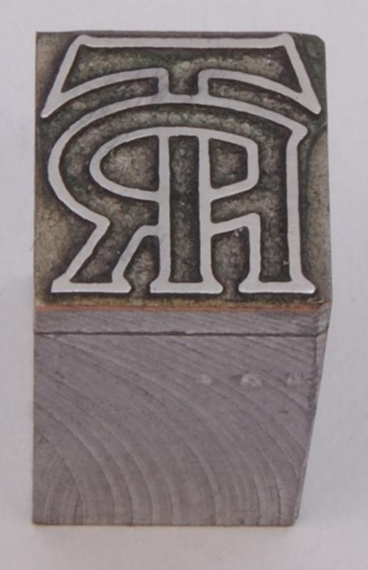 """Kliché av mörkgrå metall, monterad på en grå metallkloss. På klichén finns Trafikrestaurangers äldre logotyp med bokstäverna """"TR"""" sammanlänkade. Logotypens konturer är i relief."""