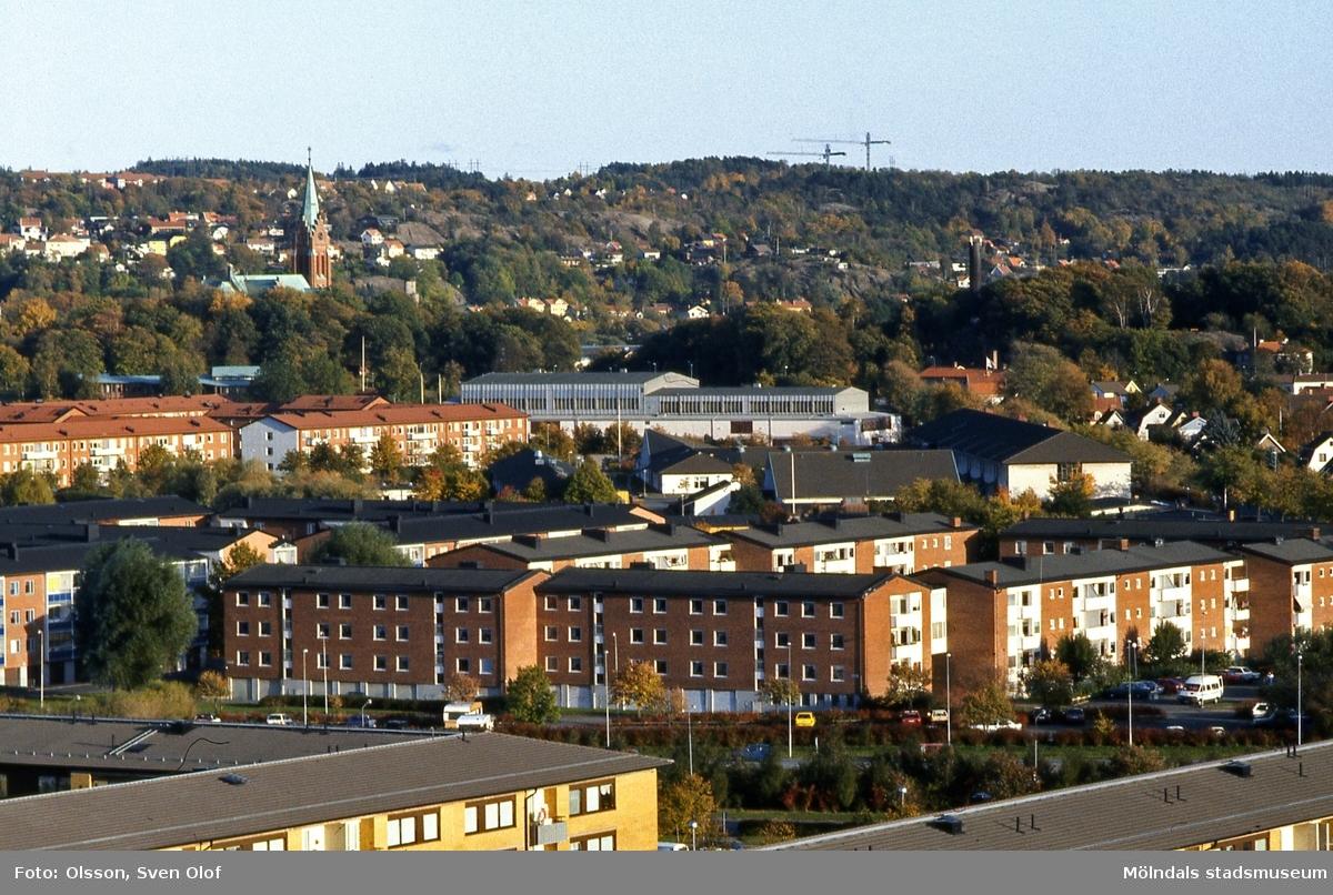 Vy genom teleobjektiv från Jungfruhoppet över bostadsbebyggelse i Bifrostområdet, vid Jungfruplatsen samt Fässbergsgymnasiet, mot idrottshuset och Fässbergs kyrka, i oktober 1992. Lägg även märke till byggkranarna på Hålsten.