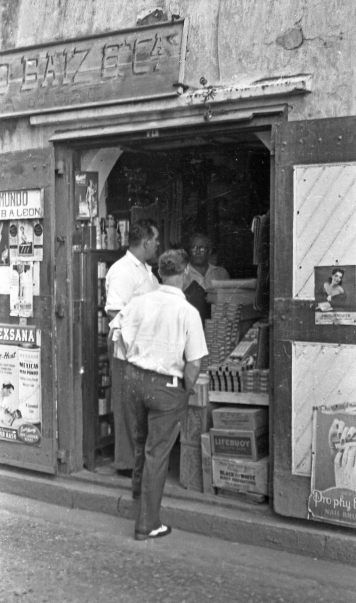 Dørhandel. To personer utenfor den lokale tobakksforretningen. Suderøy på vei til fangstfeltet.