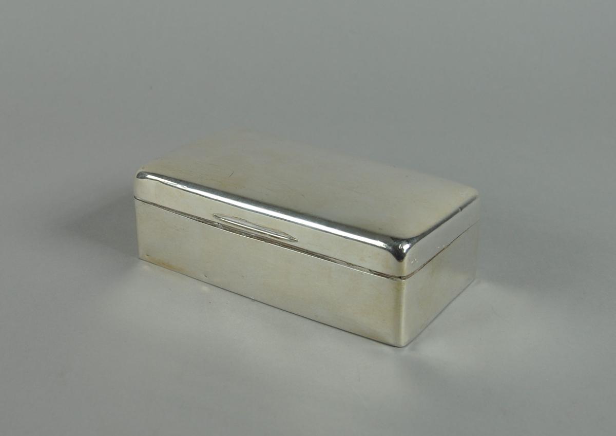 Rektangulært etui av sølv. Etuiet har avrundede hjørner og hengslet lokk. Innsiden av etuiet er innlagt med tre og har to seksjoner.