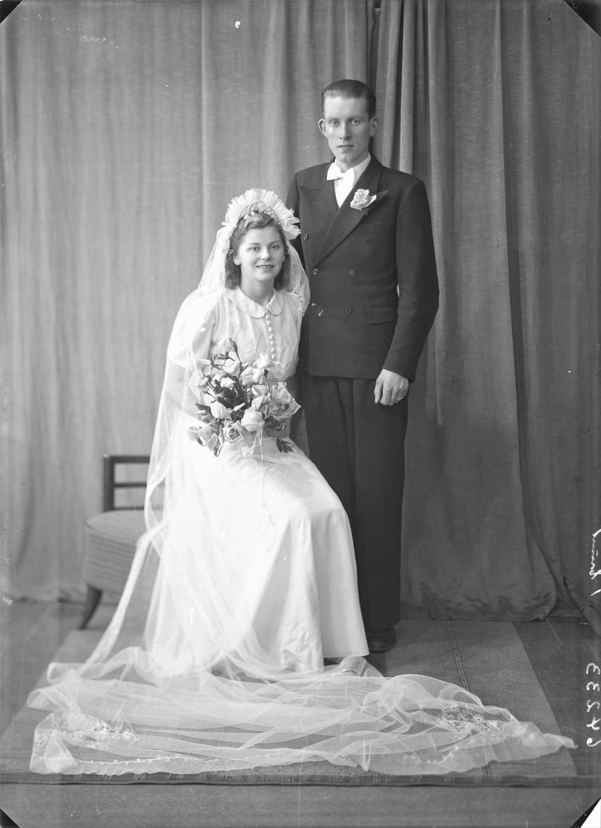Gruppebilde. Brudebilde. Ung kvinne i lang hvit brudekjole med blomsterbukett og ung mann i mørk dress, hvit skjorte og hvit sløyfe. Brudepar. Bestilt av Hr. Birger Simonsen. Skudeneshavn.