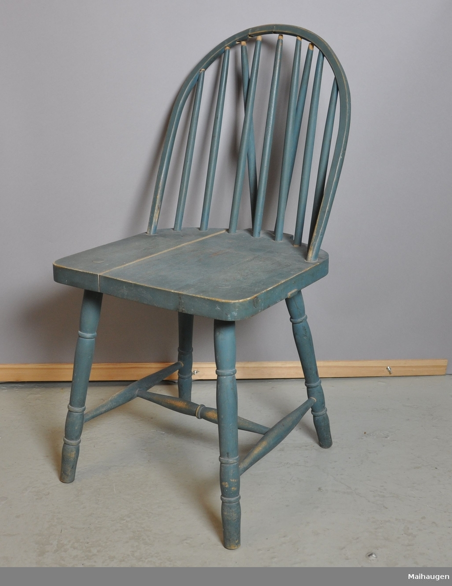 Grønn stol av tre. Setet er sprekt. Spiler i rygg og enkelte sprosser er løse. Bein og sprosser er dreid.