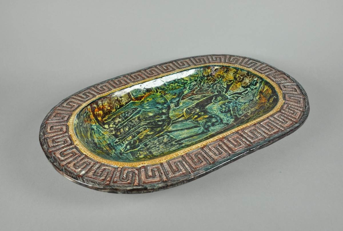 Ovalt fat av glassert keramikk. Fatet har utstående kant. Langs kanten går det en borde med gresk mønster. I fatet er det motiv av to rådyr ved et vann.