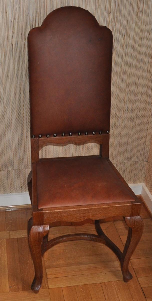 Stol av tre, med skinntrekk. Stolen har skinntrekk på rygg og sete, på ryggen er skinnet festet med nagler med store hoder. Stolen har fire kurvede bein, med h-formet kurvet sprosse. Sargene er sveifet.