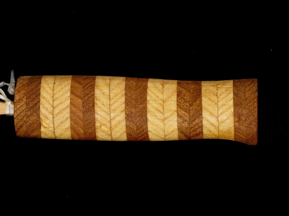 Knivskaft.  Alm og mørkere kastanje.  Skaftet er skåret av smalt stykke tre, skåret i 45 graders vinkel med årene, og limt sammen to og to stykker i samme tresort, slik at det dannes et fiskebensmønster.  Skaftet har fire (eller fem (utydelig på kortet) lyse felt i ask og fem mørke i kastanje.