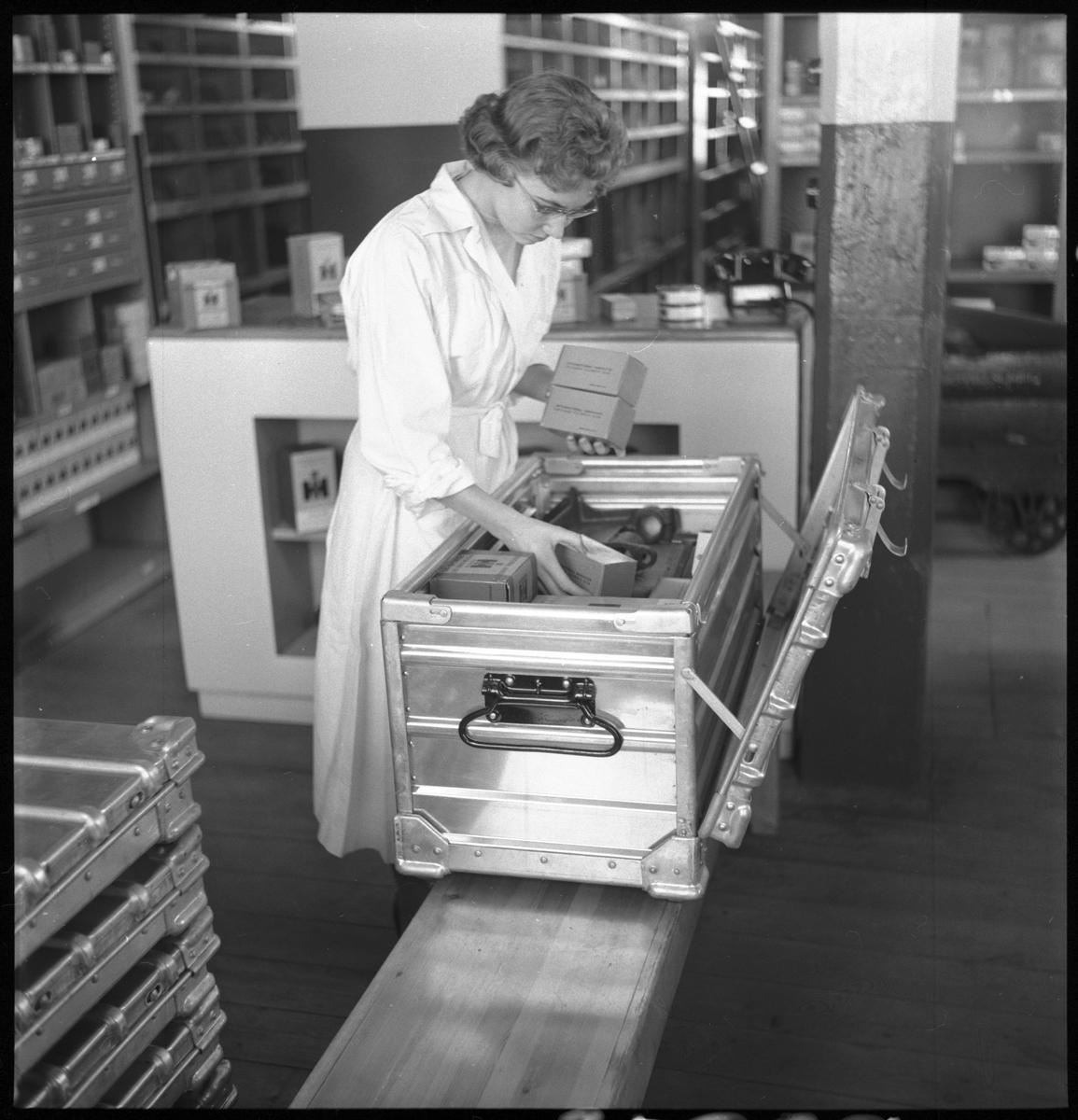 Kvinna instruerar hur man monterar småbehållare SJ La 10386, hopfällbar box av plåt.