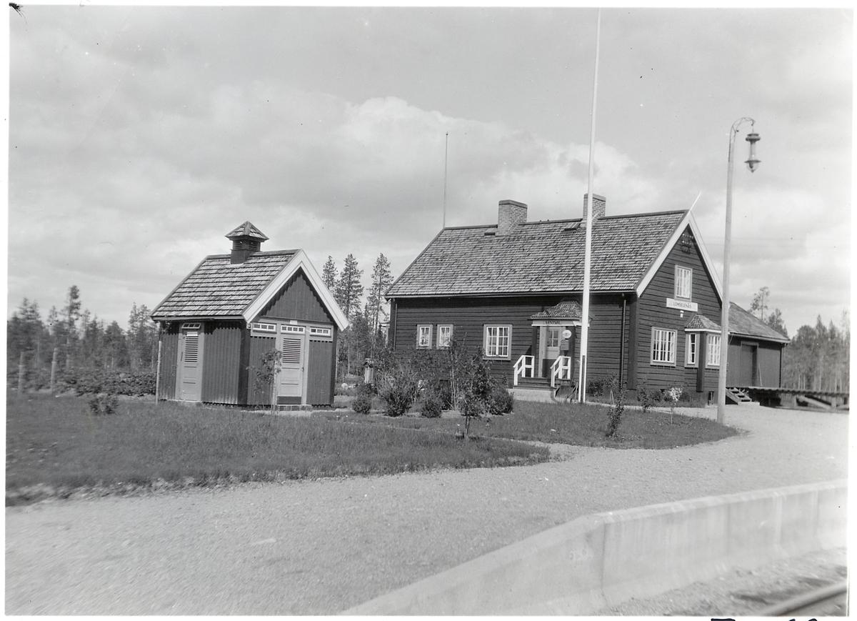 Lomselenäs är ett envånings stationshus i trä, som är sammanbyggt i vinkel med godsmagasinet.