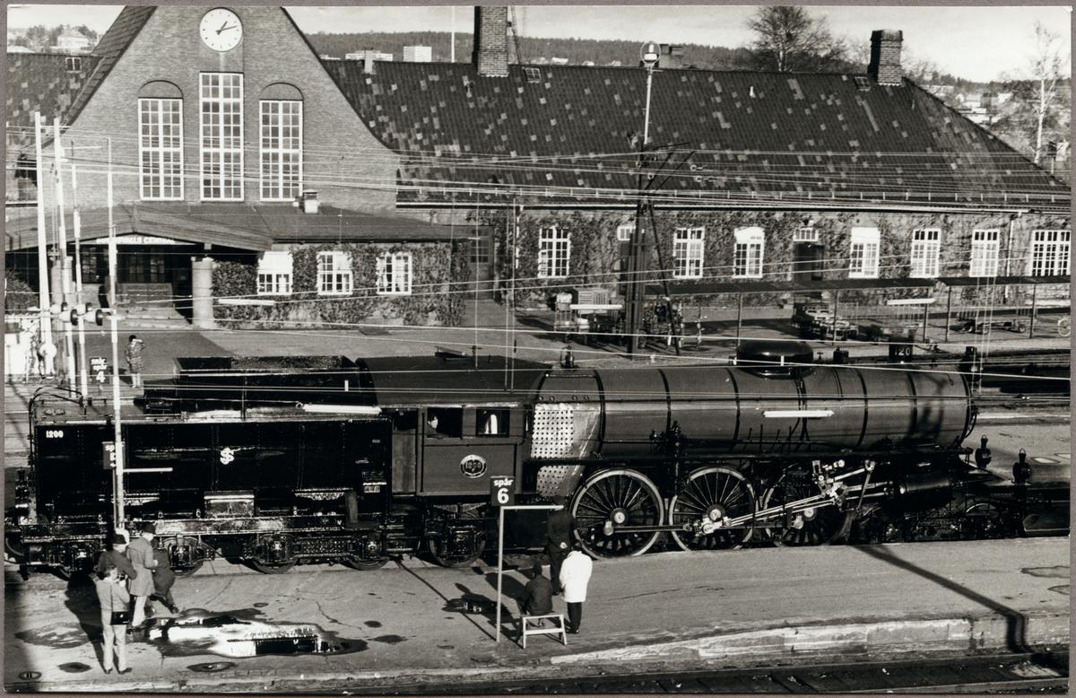 Statens Järnvägar, SJ F 1200.  Ånglok och personal vid perrong med stationshus i bakgrunden.