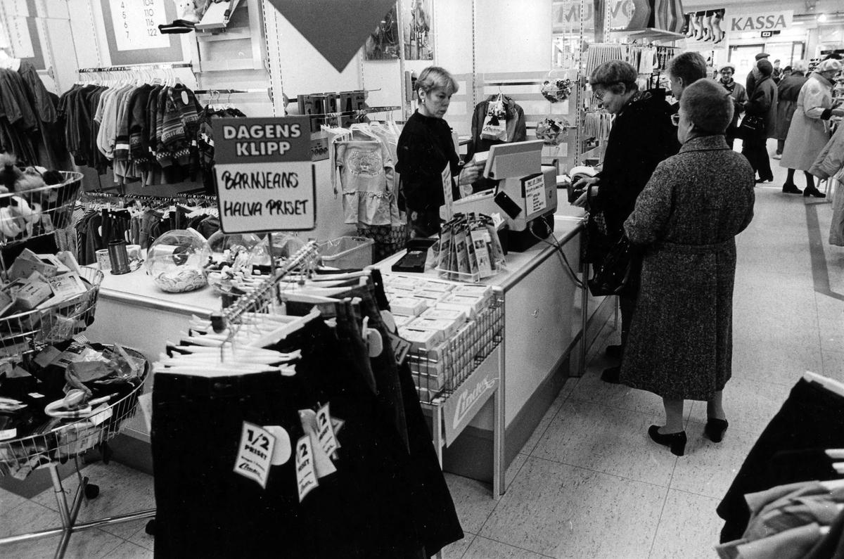 En kassörska hjälper tre damer i kö inne på Lindex, Kungsgatan 32, kvarter Pärlan 7. I november 1990 flyttade butiken tillsammans med Gulins (senare Adelsten) in i Epas gamla varuhus i kvarter Storken 12.