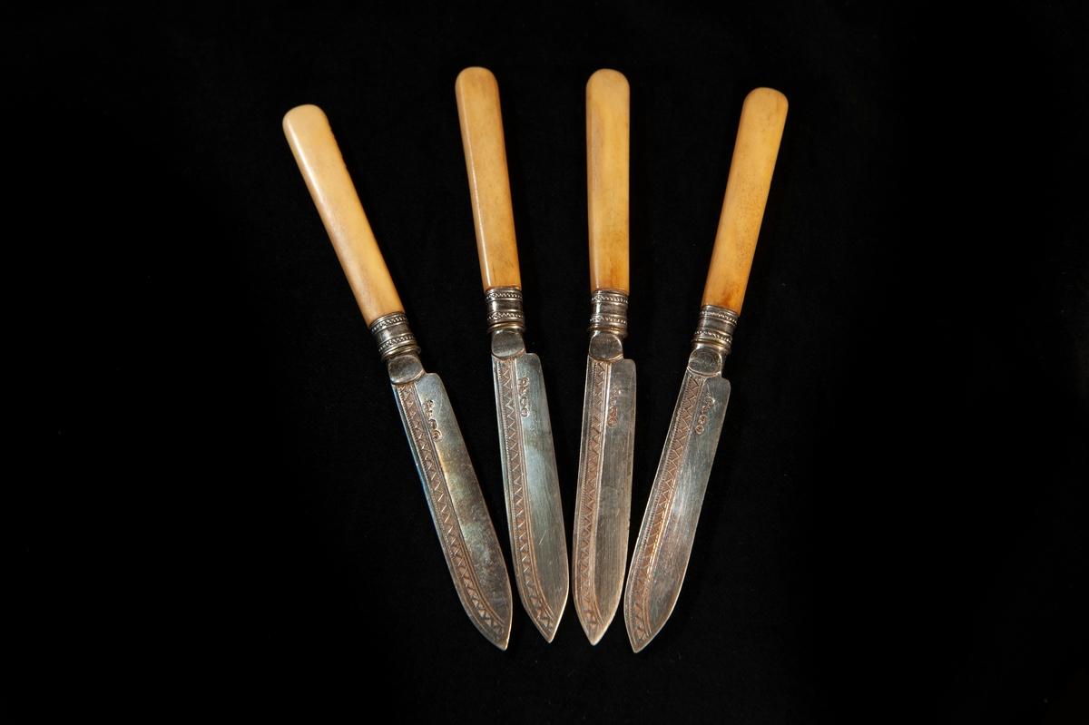 En fruktkniv av silver/nysilver med skaft i gulbeige ben. Dekor i form av zickzackbård på bladet. Otydliga utländska stämplar. Jfr JM 18876 - 18878.