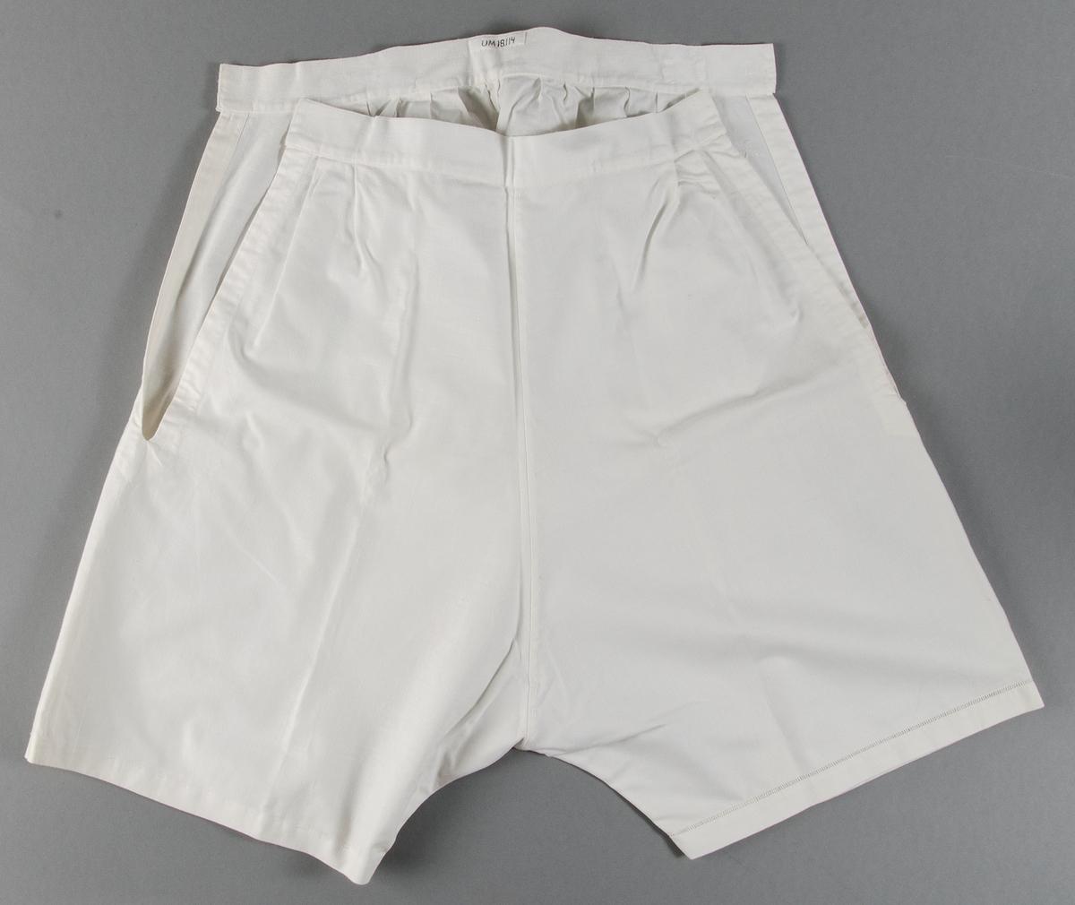 Underbyxor av vitt bomullstyg. Sprund i sidorna. Hålsöm runt höger byxben. Märkt AE i plattsöm med vitt moulinégarn, vid linningen på höger sida fram. Ej färdigsytt.
