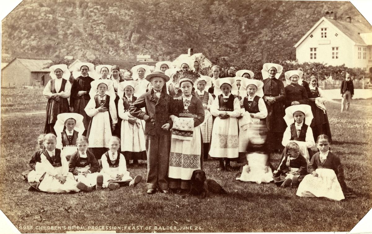 Barnebryllup i forbindelse med St. Hans-feiring, antagelig i Hardanger. De fleste jenter og kvinner bærer Hardangerdrakt. Fotografert mellom 1870 og 1886.