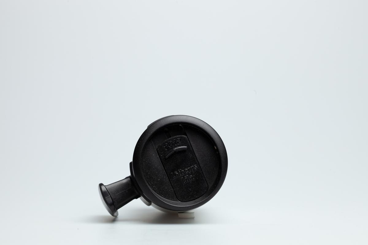 Et sort skrulokk på en Statoilkopp fra 2012. Skrulokket har en mekanisme som kan stenge og lukke for et lite hull, der man kan drikke kaffe igjennom. På skrulokket står det 2012 og Löfbergs Lila.