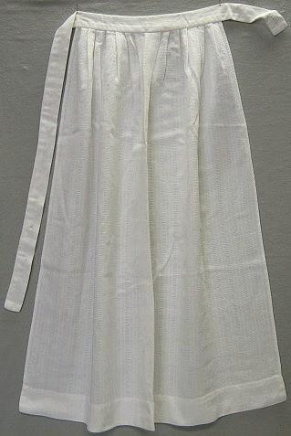 Förkläde till Hedemora kvinnodräkt. 98,5 cm lång, 3,5cm bred linning som knäpps i sidan med en plastknapp. Fållen mäter 5 cm. Smala fållar i sidorna. Lagda veck i midjan.