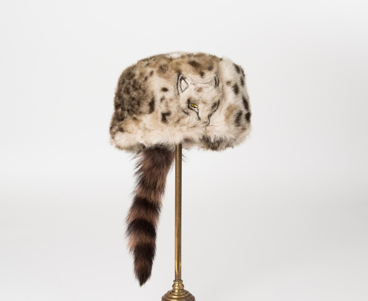 """Barnmössa av leopardmönstrad fuskpäls, framtill på mössan är ett rävhuvud broderat. Bak på mössan är en tvättbjörnsvans påsydd. Foder av mönstrat tyg. Öronlappar av brunt ylletyg. Isydda etiketter: """"wigéns AB Oscar Wigén i Tranås."""", och """"wigéns 48 MADE BY WIGENS"""". Vidhängande pappersetiketter: """"wigéns AB Oscar Wigén i Tranås."""", och """"wigéns MODELL 98056 KVALITÉ 560308 STORLEK/SIZE 48 PRIS 159:-""""."""