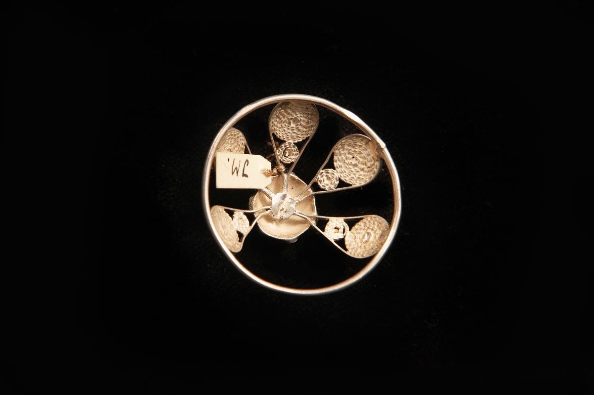 """En malja av silver. Glest filigranarbete i fem st. """"tungor""""upp mot liten blomma i filigran.Stämplad på rundelns kant. JM.19973:a-e hör ihop."""
