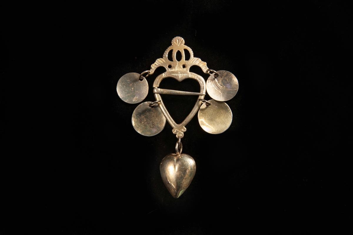 """Ett hjärtformat spänne av förgyllt silver. Genombruten stiliserad krona upptill. 4 skålar (varav de övre är graverade på ena sidan) hänger från spännet.   Längst ner ett hjärta av silver (med annan stämpel:""""E.E.., (Växjö) """" (= Eric Ekström, Växjö (verksam 1819 - 1840 ca )"""