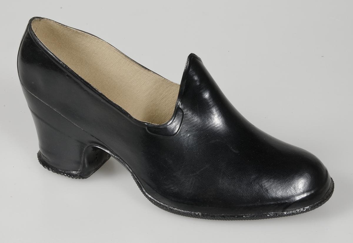 Pampusch av svart gummi för kvinna. Skomodell med hög snibb mitt fram över  vristen. 0367e9ee6758c