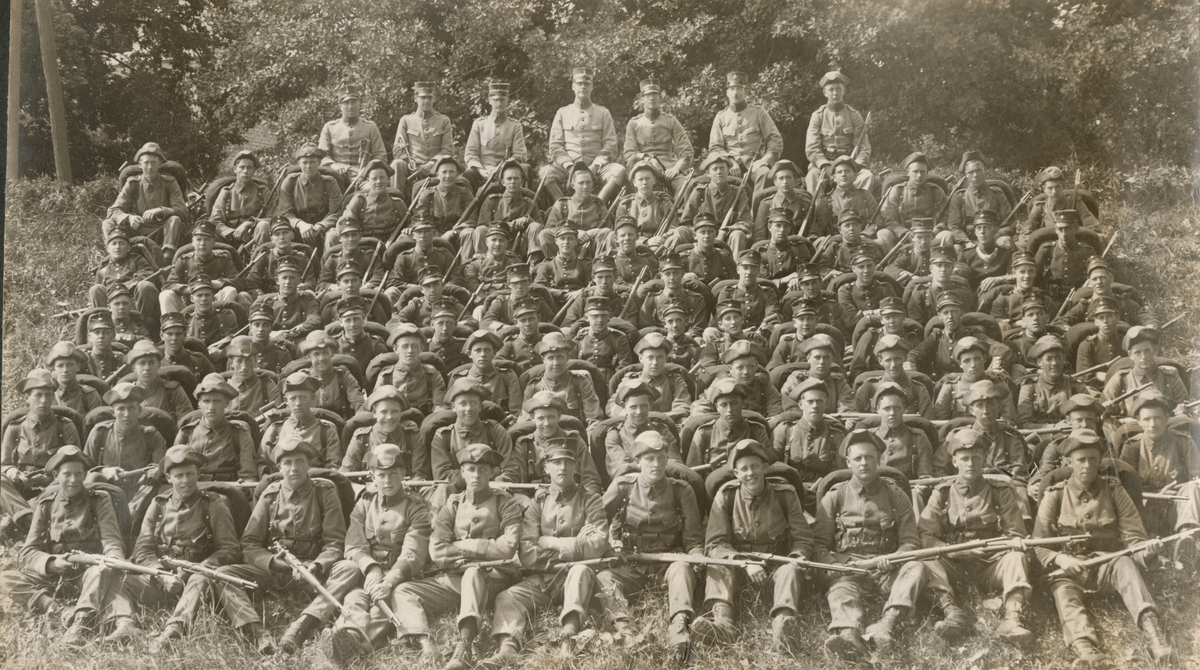 """Bildtext: """"Sommaren 1921. 8. komp. Fr. v.: serg. Svensson, U. ljt. Kjellberg, Ego (Allan Hasselrot), kpt. Hederén, ljt. Remahl, fanj. Roth, furir Ason. Översta raden värnpliktiga: granatkastarplutonen."""""""