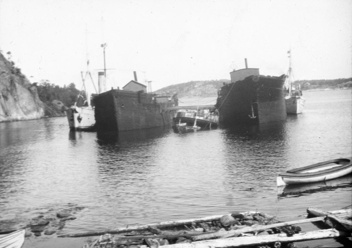 To store fartøy, med to mindre dampskip fortøyd til hvert av fartøyene. I midten to mindre farkoster. Skipsbergning.