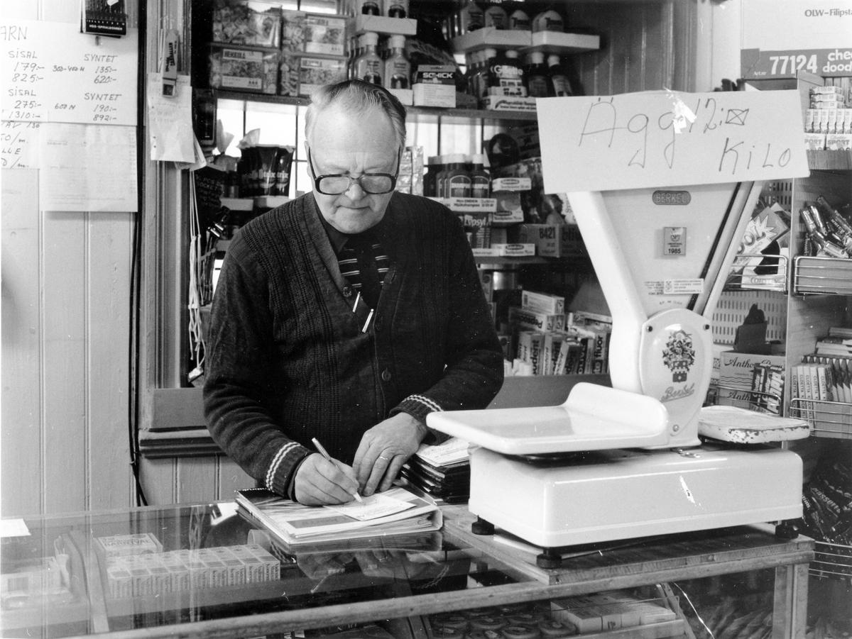 Bild innifrån Gunnar Johansson KB i kvarter Repslagaren 2 där specerier, jordbruks- och trädgårdsprodukter säljs. Ägaren Gunnar Johansson står vid en våg och skriver.