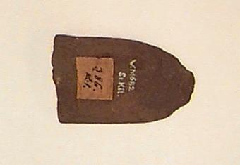 Baneparti, tvärt avbrutet (eggpartiet saknas). Av finkornig brunaktig bergart. Slipat. Ovalt tvärsnitt.