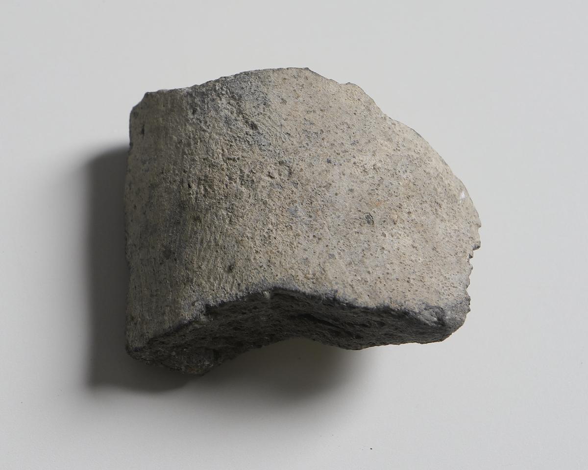 Bukfragment av stengodskärl med ljusgrå glasyr på kärlets insida och utsida.