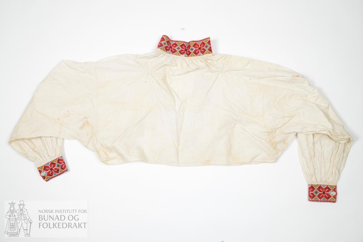 Skjorte av bomullslerret, all samansying og indresaumar sydd for hand med små nette sting. Innfelte halskilar og ermekilar. Broderte kvardar med anelinfarga ullgarn, sydd med korssting gjennom eitt lag stoff, og fora med bomullslerret. Kvardane sydd på for hand, og rynka for hand. Djup halssplitt mf.