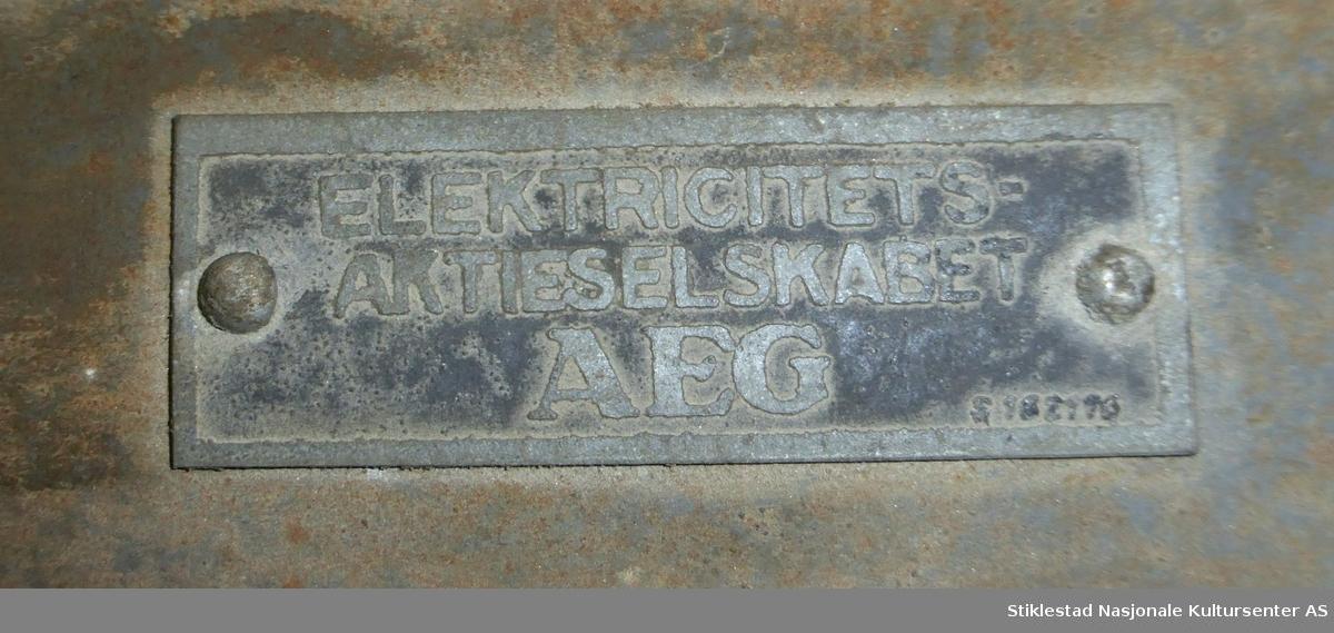 """Vedkappsag med elektrisk motor fra AEG. Saga er montert på to trekantete bokker laget av bokser/bjelker i gran. Sagblad er montert i motsatt ende av motoren. Kappsaga fungerer ved at man legger veden/""""strangen"""" i """"vogga"""" mens man fører denne mot det tverrstilte sagbladet. Forholdsvis lite sagblad."""