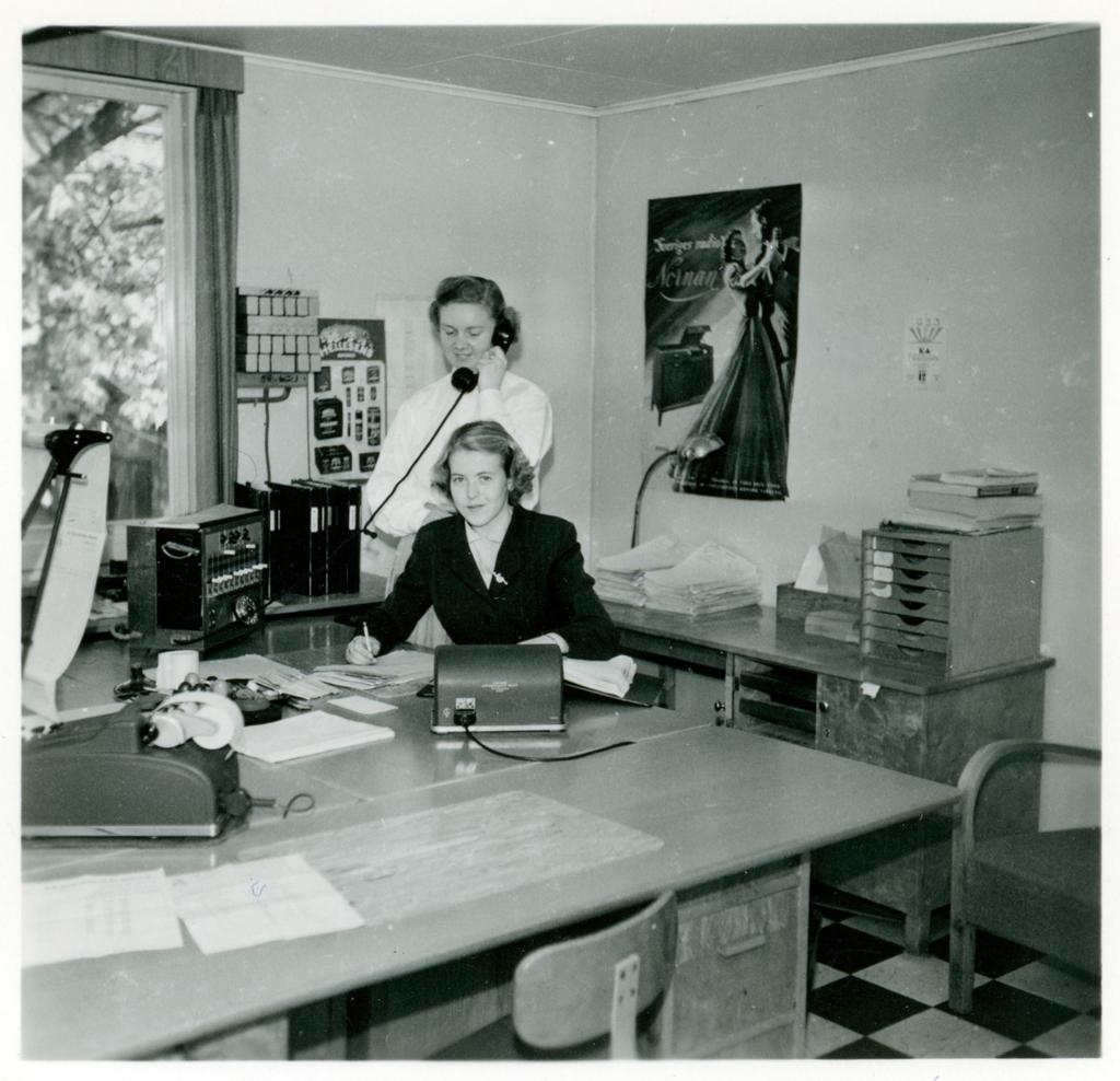 """Två av kontorspersonalen på Monarks kontor. Den ena kvinnan står och talar i telefon, Gunnel Andersson sitter ner och tittar in i kameran. Bakom dem på väggen sitter en affisch med reklam för Monarks radiomöbel """"Nornan""""."""