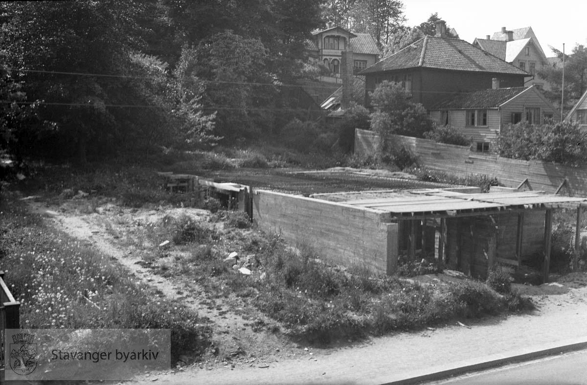 Byggeplass, muligens på Våland. Det kan være Lagårdsveien som skimtes i forgrunnen. Sveitservilla i bakgrunnen.