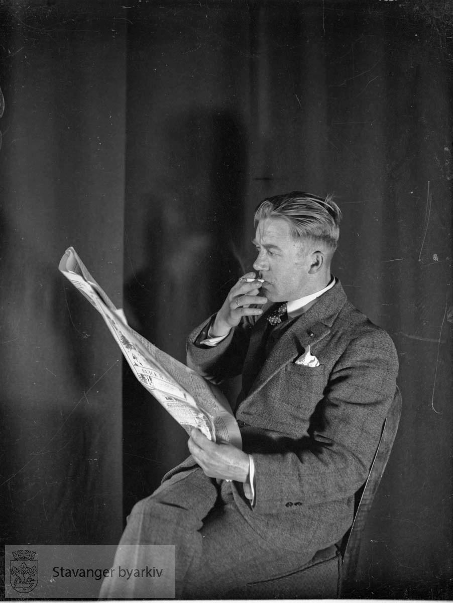 Mann røyker og leser avisen