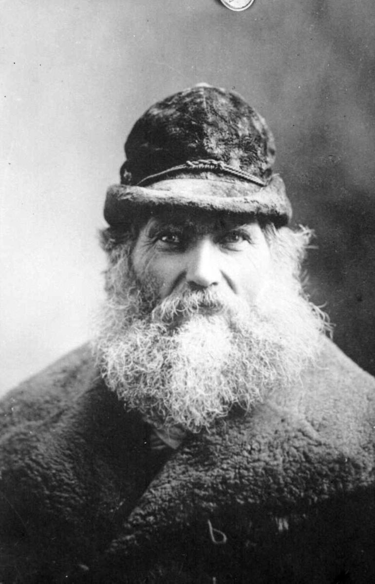 Portrett av eldre mann med stort skjegg.