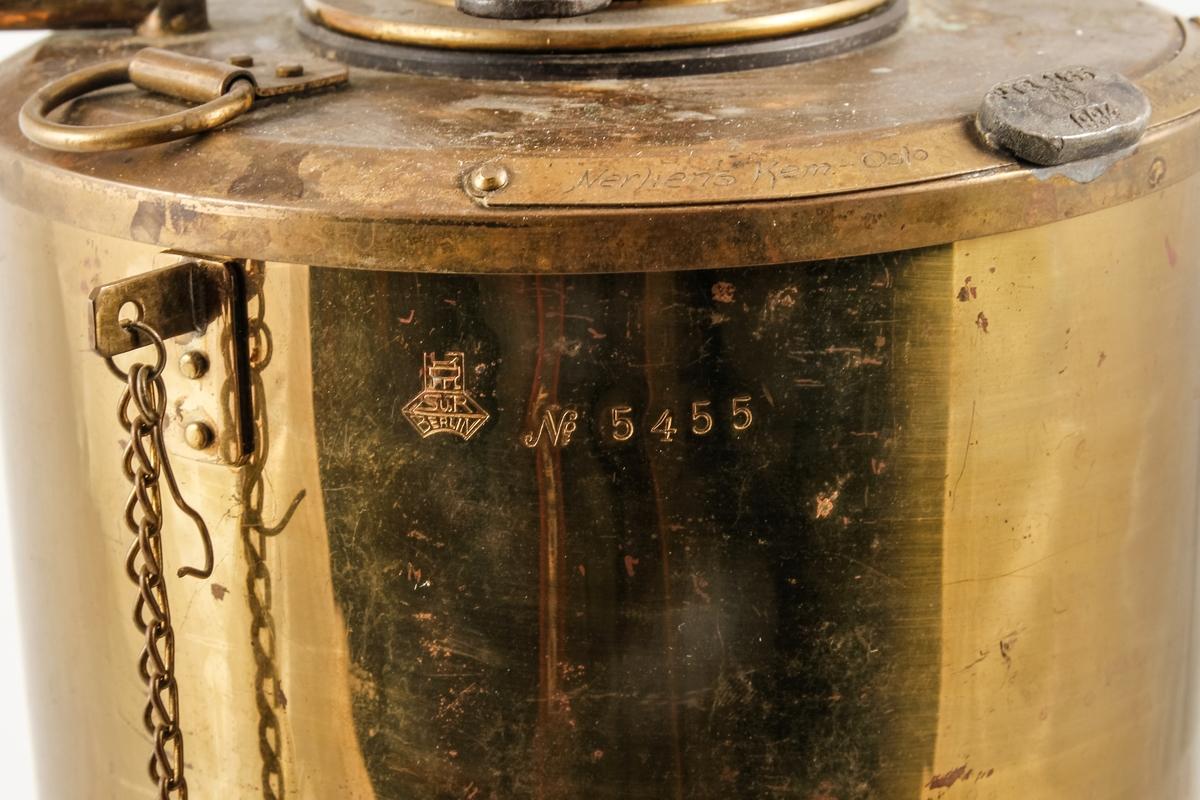 Kjemisk måleinstrument framstilt i messing brukt til å måle såkalt flammeflukt. Instrumentet har bøtteform og består av 5 ulike deler og synes å involverer en eller annen form for oppvarming? Hovedelementet står på 3 føtter med skruehull slik at instrumentet kan festes til et underlag. Opprinnelig har instrumentet også hatt 2 thermometer (für Petroleumsproben).
