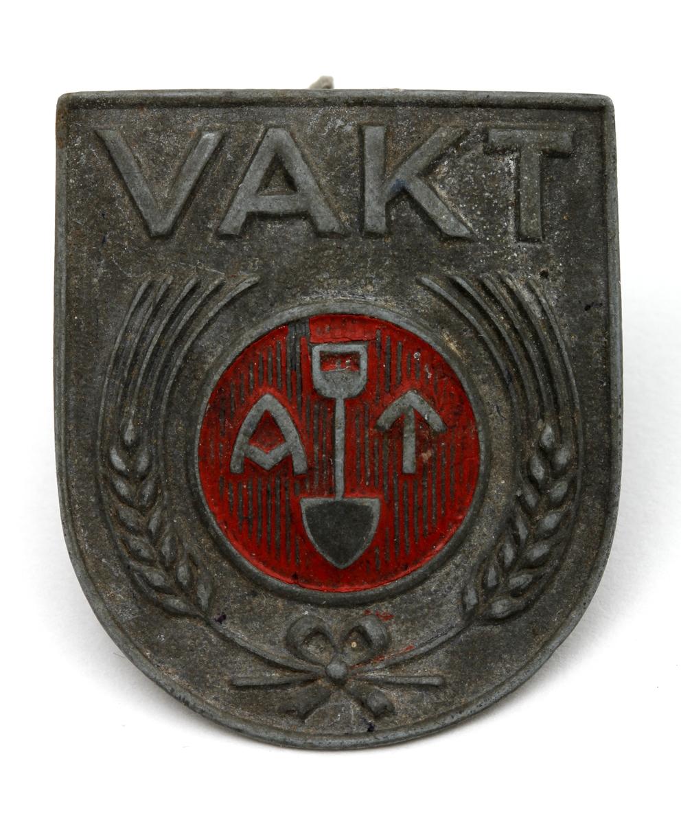 Et tungeformet jakkemerke i metall brukt under 2. verdenskrig i den tyske arbeidstjenesten. Over det runde og røde symbolet til arbeidstjenesten - med avbildning av en spade mellom bokstavene A og T,  står det VAKT. Symbolet omkranses av to sambenbundede kornaks. Merket skal maljes til arbeidstøyet.