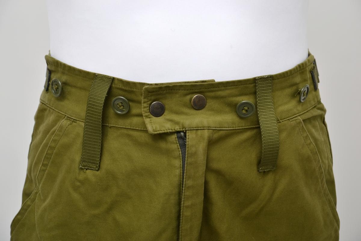 Militærgrønn feltbukse i bomull med snorelukking nede ved anklene. Buksen har forsterkninger foran på lår og setet. Lukking med glidelås og trykknapper og regulering i midje med spenner. Knapper langs linning til seler. To stikklommer foran og ei bak samt lomme med klaff på lår.