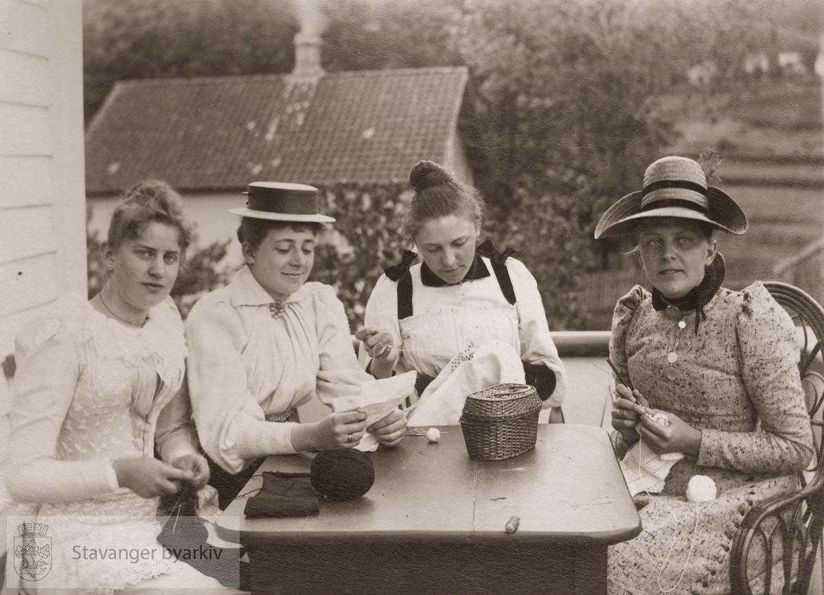 Fire kvinner med strikketøy sitter ved bordet på altanen.