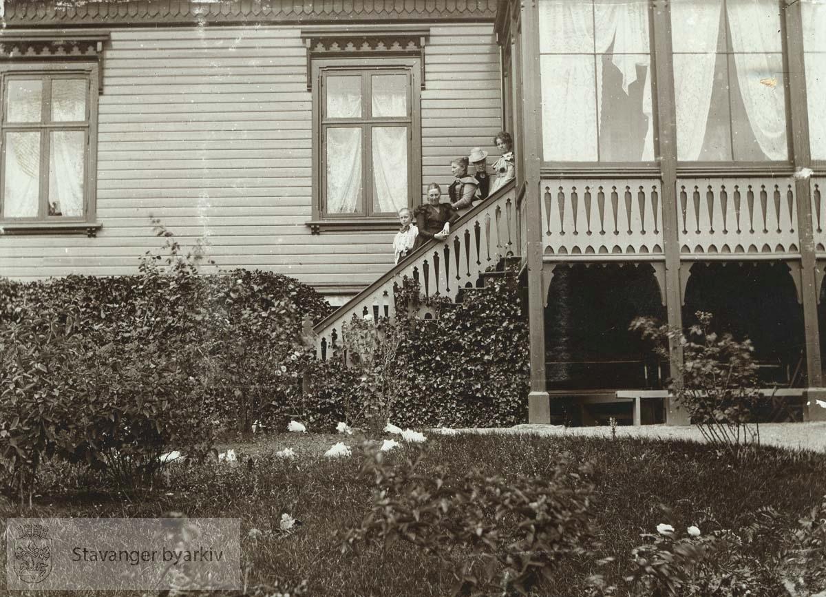 Kvinner av familien Monsen står i trappen opp til glassverandaen.