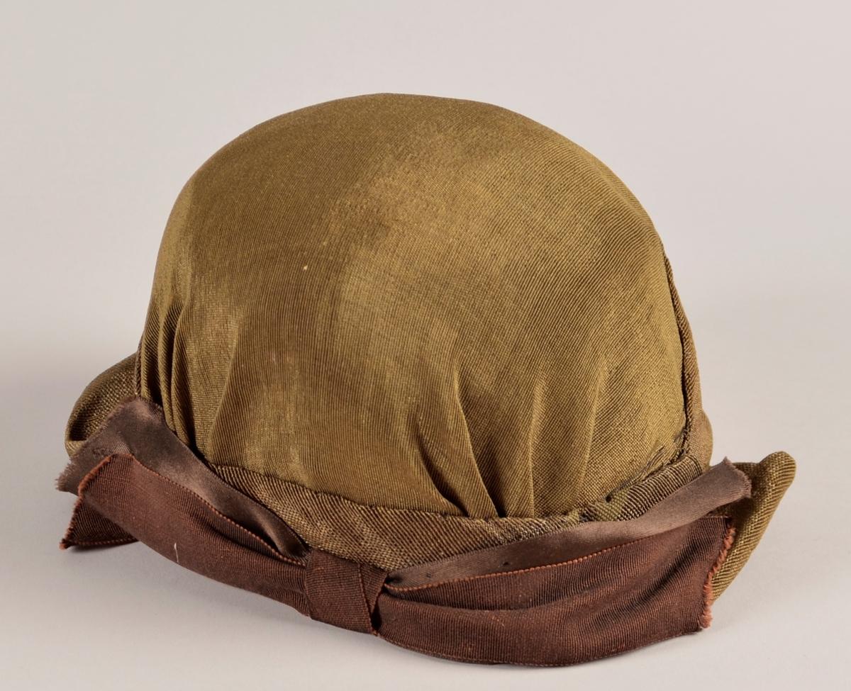 Kvinnehatt. Stiv materiale. Utsida i gyllent, svart/gull, stoff. Sløyfe på sida av brunt band. To gule blad av fløyel til pynt på andre sida. Svart fôr.