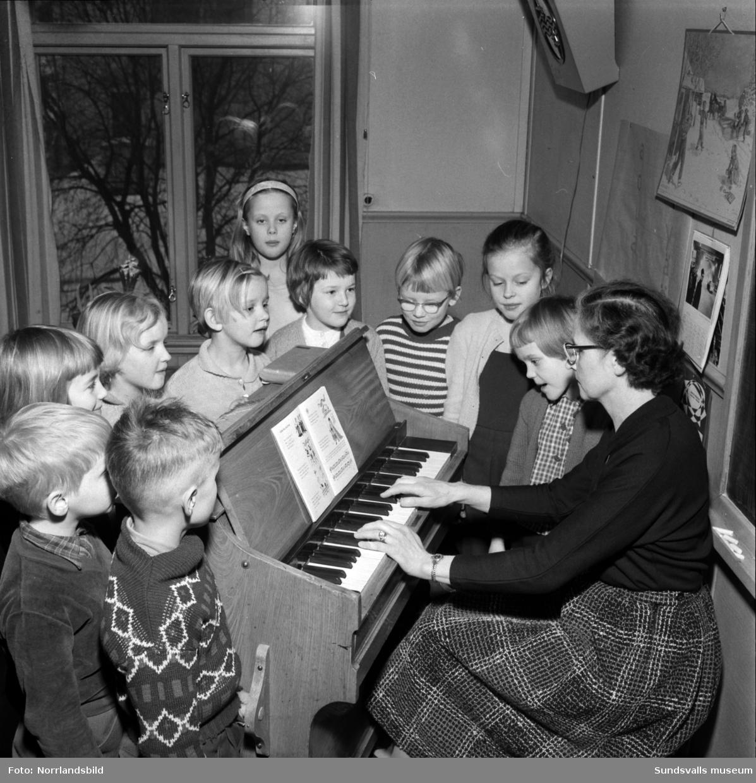 Kubikenborgs förstaklassare med sin fröken är samlade runt skolorgeln.