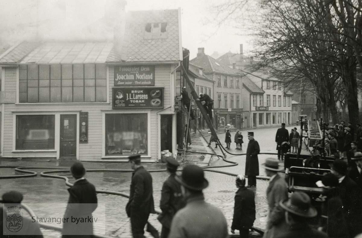 Brann i Kongsgaten 24. Fotograf Joachim Norlands atelier og butikk. Brannmenn i stige prøver å slukke brannen. Fotografiet er i album.